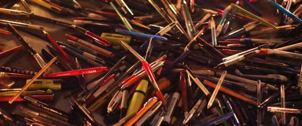 A pile of pens, representing the journalism and caricaturist professions, are scattered on the ground as people gather to commemorate the victims and condemn the killings at the French magazine Charlie Hebdo, on the Place de la République in Paris, France, 07 January 2015.    Source: EPA/Fredrik Von Erichsen