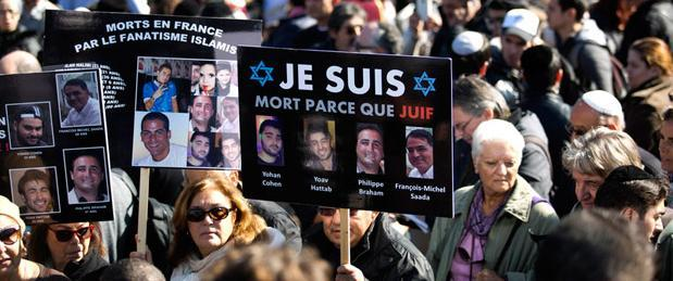 Participants hold signs with pictures of the victims and reading, 'Je suis mort parce que juif' (I died because I am Jewish) during the funeral of the four Jews killed in the Paris kosher supermarket during the funeral ceremony at the cemetery in Jerusalem, 13 January 2015.   Source: EPA/ABIR SULTAN