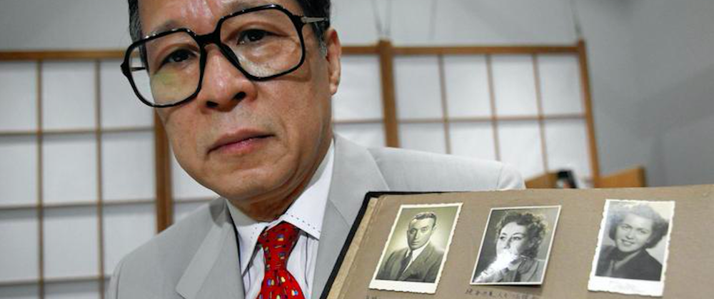 Akira Kitade, in July 2010, holds an album showing seven of those helped by former colleague Tatsuo Osako. (Shizuo Kambayashi / Associated Press)