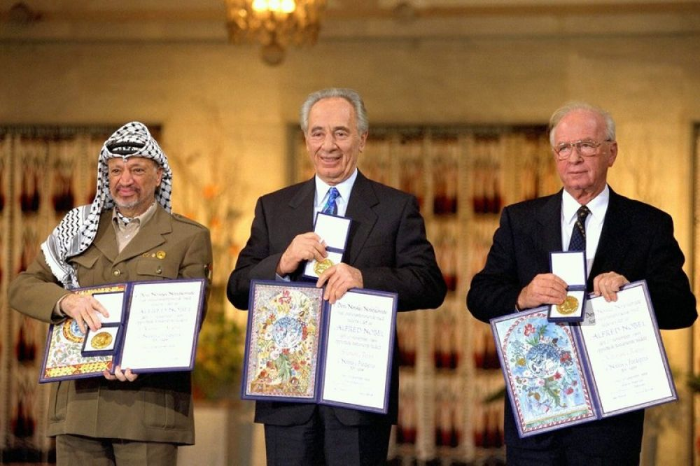 Слева направо: палестинский лидер Ясир Арафат, министр иностранных дел Израиля Шимон Перес и премьер-министр Израиля Ицхак Рабин на вручении Нобелевской премии. Фото EPA